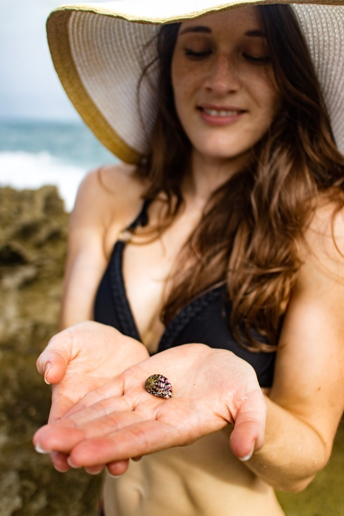 A young woman holds a multi-colored snail in her hands. She is wearing a hat and looking down at the snail. There is a bit of ocean in the background.